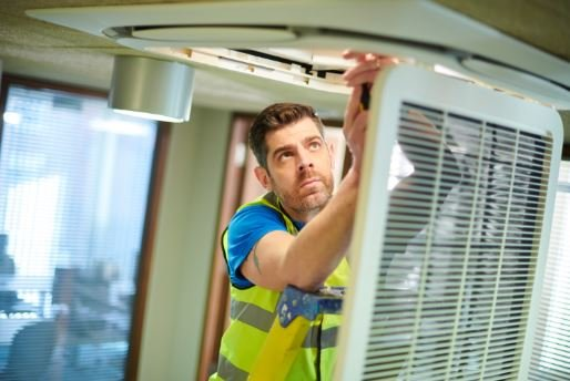 Engineer installing an air conditioning system
